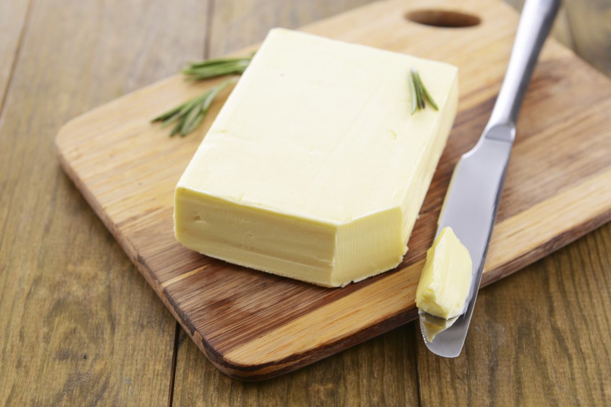 Tasty butter on wooden cutting board